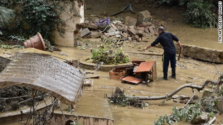 A man piles wrecked furniture outside his home in the Livorno area, flooded after heavy rain, on September 10, 2017.