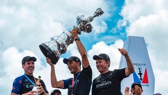 Emirates Team New Zealand helmsman Peter Burling and trimmer Blair Tuke and shore crew manager Sean Regan hoist the America