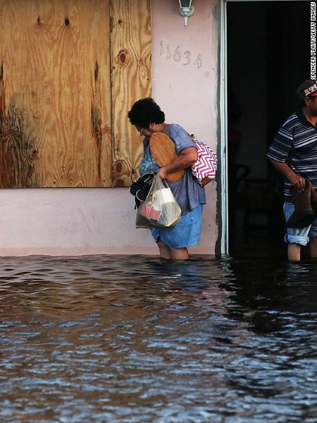 BONITA SPRINGS, FL - SEPTEMBER 11: A couple leave their flooded home the morning after Hurricane Irma swept through the area on September 11, 2017 in Fort Myers, Florida. Hurricane Irma made another landfall near Naples yesterday after inundating the Florida Keys. Electricity was out in much of the region with localized flooding.  (Photo by Spencer Platt/Getty Images)