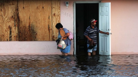 People step out of their flooded home in Fort Myers, Florida, on September 11.