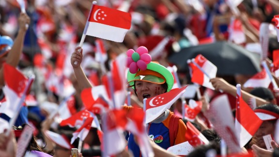 Spectators wave Singaporean national flags during their country's 52nd National Day parade and celebration in Singapore on August 9, 2017. / AFP PHOTO / ROSLAN RAHMAN        (Photo credit should read ROSLAN RAHMAN/AFP/Getty Images)