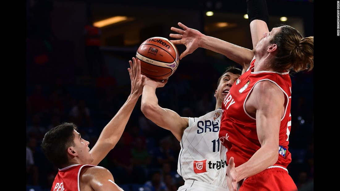 Serbian forward Vladimir Lucic, center, is defended by Hungary's Akos Keller, left, and Zoltan Perl during a EuroBasket game in Istanbul on Sunday, September 10. Serbia won 86-78 to advance to the quarterfinals.