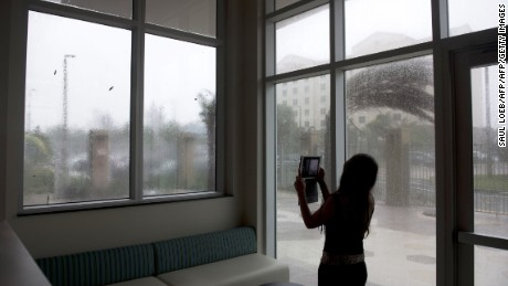 A woman uses an iPad to record heavy winds and rain from Hurricane Irma as they hit a hotel in Miami, Florida, September 10, 2017. Hurricane Irma's eyewall slammed into the lower Florida Keys, lashing the island chain with fearsome wind gusts, the US National Hurricane Center said. / AFP PHOTO / SAUL LOEB        (Photo credit should read SAUL LOEB/AFP/Getty Images)