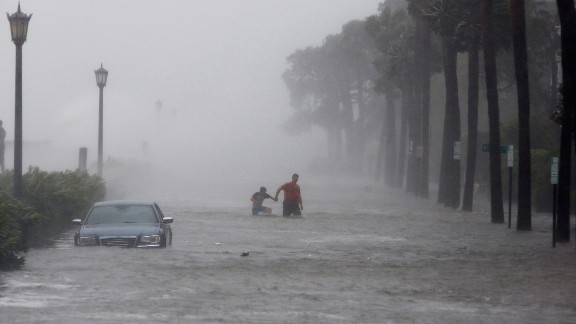 Pedestrians walk by a flooded car on a street as Tropical Storm Irma hits Charleston, S.C., Monday, Sept. 11, 2017. (AP Photo/Mic Smith)