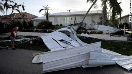 Rick Freedman checks his neighbor's damage from Hurricane Irma on Marco Island, Florida.
