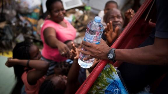 French firemen provide bottles of water to inhabitants of the Sandy Ground area of Marigot, on September 10, 2017 on Saint-Martin island, devastated by Hurricane Irma.