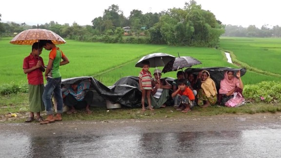 Rohingya refugees sit by the roadside, awaiting entrance into a refugee camp in Bangladesh.