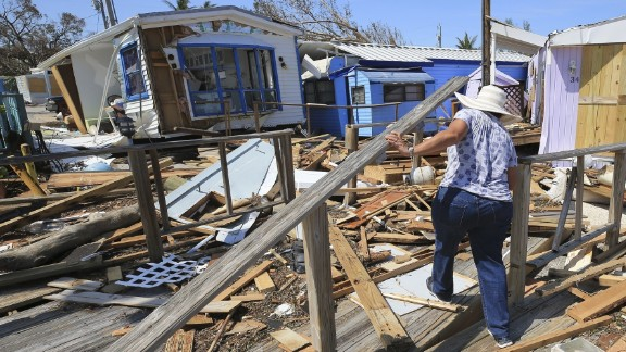 Mirta Mendez walks through the debris at the Seabreeze trailer park along the Overseas Highway in the Florida Keys on Tuesday, Sept. 12, 2017. Florida is cleaning up and embarking on rebuilding from Hurricane Irma, one of the most destructive hurricanes in its history. (Al Diaz/Miami Herald via AP)