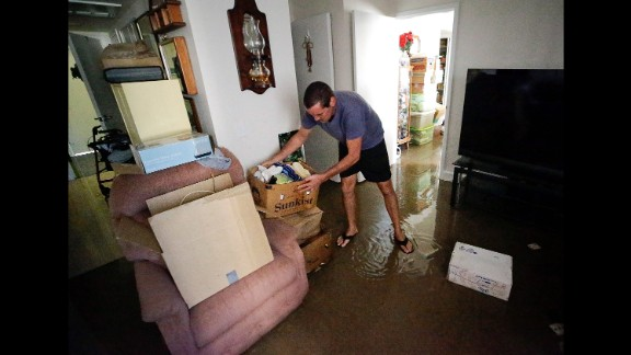 Joseph Dupuis III stacks boxes off the floor in his parents' water-logged apartment in Jacksonville, Florida, on September 12.
