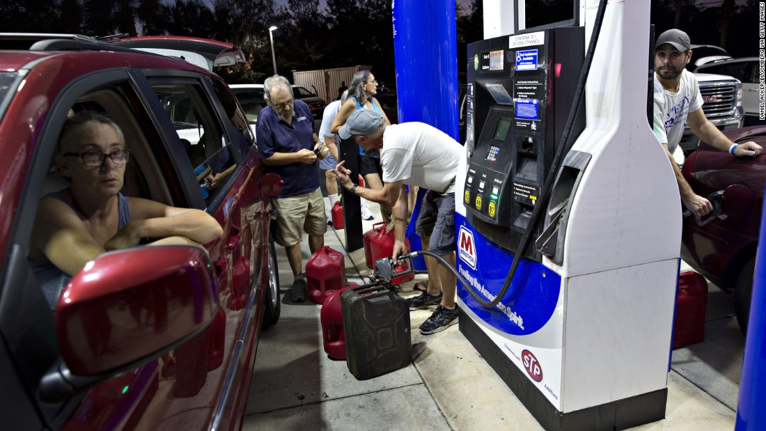 Motorists in Estero, Florida, fill gas cans September 12, moments before police shut the station down because of a curfew.