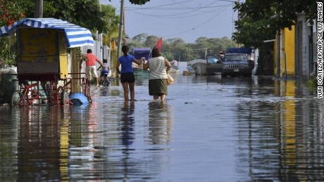 TOPSHOT - Residents walk in a street flooded by the overflow of the Tecolutla river the day after the passage of Hurricane Katia, in Tecolutla, Veracruz state, Mexico on September 9, 2017.  Katia made landfall in the east as a Category One hurricane and hours later was downgraded to a tropical storm with maximum sustained winds of 45 miles (70 kilometers) per hour. / AFP PHOTO / YURI CORTEZ        (Photo credit should read YURI CORTEZ/AFP/Getty Images)