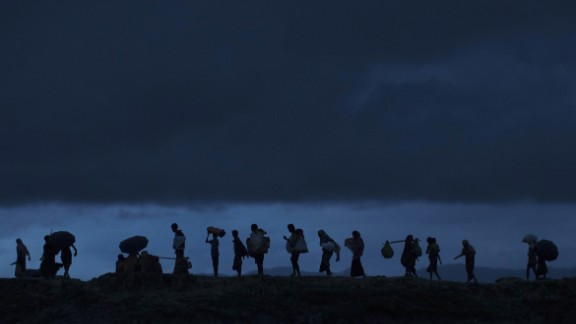 GUNDUM, BANGLADESH - SEPTEMBER 09:  Rohingya refugees walk across Paddy fields at dusk after crossing the border from Myanmar on September 09, 2017 in Gundum, Bangladesh. Recent reports have suggested that around 290,000 Rohingya have now fled Myanmar. Those who left have spoken of violence erupting in Rakhine state, when the country's security forces allegedly launched an operation against the Rohingya Muslim community.  (Photo by Dan Kitwood/Getty Images)