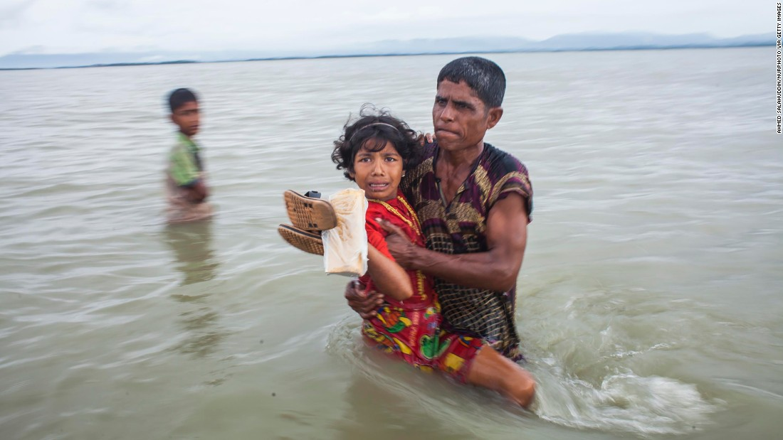 A girl is carried to safety after crossing the Naf River on September 9.