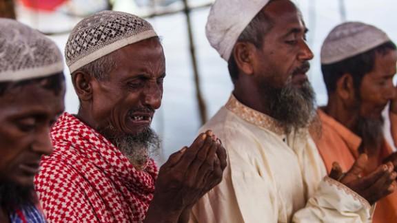 Rohingya men pray on September 11, in a makeshift shelter near Cox's Bazar.