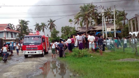 This picture taken on August 27, 2017 shows onlookers watching as firefighters attempt to extinguish fires from houses burnt by Rohingya militants in Maungdaw township in Rakhine State in Myanmar.Myanmar's Aung San Suu Kyi on August 28 accused Rohingya fighters of burning down homes and using child soldiers during a recent surge in violence in troubled Rakhine state, allegations denied by the militants themselves. / AFP PHOTO / STR        (Photo credit should read STR/AFP/Getty Images)