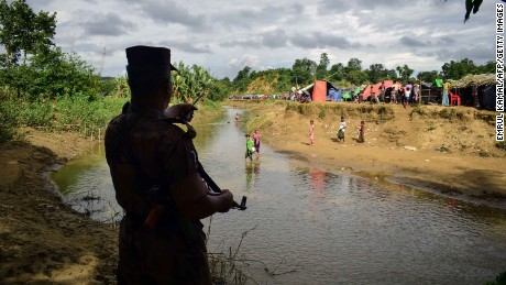 This August 29, 2017 photo taken from Nykkhongchhari near the Bangladeshi town of Ukhiya shows a Bangladeshi border guard ordering Rohingya refugees to return to the Myanmar side of a small canal between the two countries.