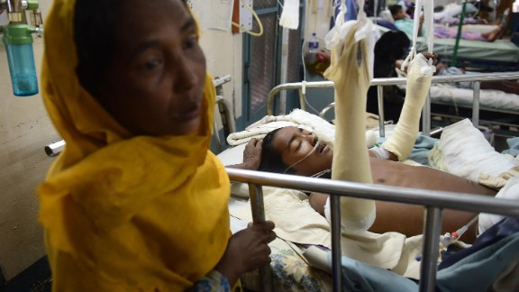 Rohingya refugee Rashida Begum stands next to her 15-year-old son, Azizul Hoque, as he is treated on September 13, at a hospital in Cox's Bazar, Bangladesh. He sustained a landmine injury while crossing from Myanmar to Bangladesh.