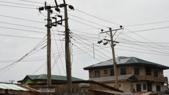 Public power cables and transformers stand across solar panels mounted on the roof top of a building as an alternative power supply in Lagos.