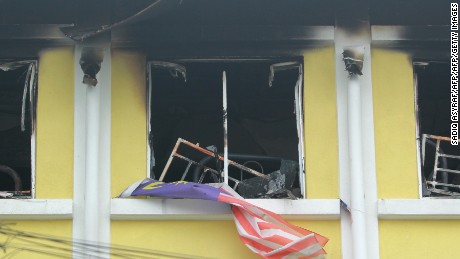 A Malaysian national flag flutters outside burnt windows of the Darul Quran Ittifaqiyah religious school in Kuala Lumpur on September 14, 2017.  Twenty-five people, mostly teenage boys, were killed on September 14 when a blaze tore through a Malaysian religious school, in what officials said was one of the country's worst fire disasters for years. / AFP PHOTO / SADIQ ASYRAF        (Photo credit should read SADIQ ASYRAF/AFP/Getty Images)