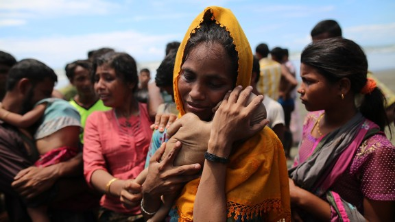TEKNAFF, BANGLADESH - SEPTEMBER 13 : A Rohingya Muslim woman holds an infant child who died when the boat they were traveling in capsized just before reaching the shore of the Bay of Bengal, in Shah Porir Dwip, Bangladesh on September 13, 2017. Violence erupted in Myanmars Rakhine state on Aug. 25 when the countrys security forces launched an operation against the Rohingya Muslim community. It triggered a fresh influx of refugees towards neighboring Bangladesh, though the country sealed off its border to refugees.  (Photo by Zakir Hossain Chowdhury/Anadolu Agency/Getty Images)
