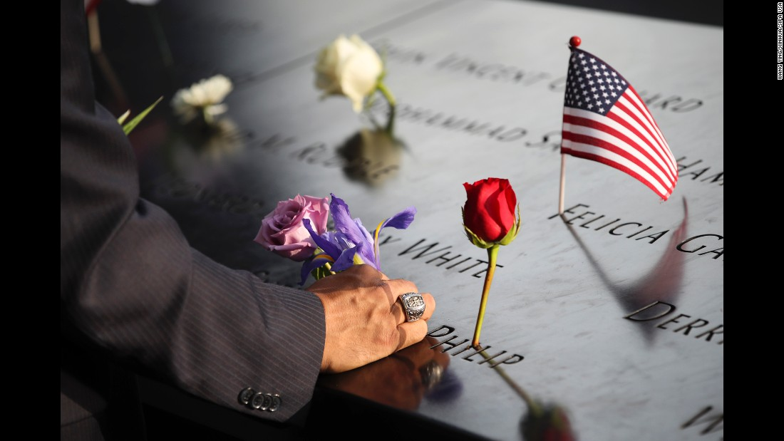 On the 16th anniversary of the 9/11 attacks, a man places a flower at the National September 11 Memorial in New York.