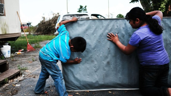 Children clean a dirty mattress from a flooded home in Immokalee, Florida, on Thursday, September 14. Hurricane Irma laid waste to beautiful Caribbean islands and caused historic destruction across Florida. The cleanup will take weeks; recovery will take months.