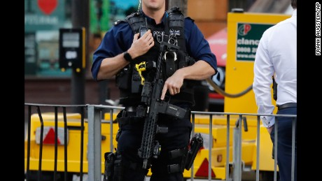 An armed police officer stands nearby after an incident on a tube train at Parsons Green station.