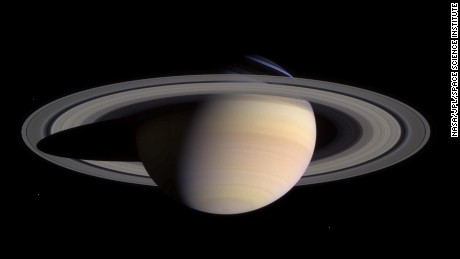 Saturn's pale colors and its rings come into view as Cassini approaches on May 7, 2004. This composite was made from images taken when Cassini was about 18 million miles (29 million kilometers) from Saturn. The small white dots are some of Saturn's moons.