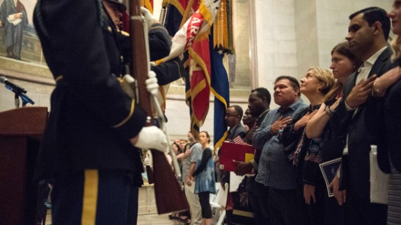 New US citizens listen to the national anthem during a naturalization ceremony at the National Archives in Washington, DC, on September 15, 2017. (NICHOLAS KAMM/AFP/Getty Images)