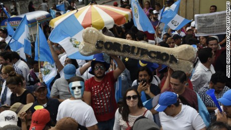 People take part in a protest demanding the resignation of congressmen outside the Guatemalan National Congress, in Guatemala City on September 15, 2017.  Guatemala's congress early this week, voted overwhelmingly to reject a UN-backed request to lift the immunity of President Jimmy Morales in order for him to face a corruption probe over irregular party financing. / AFP PHOTO / JOHAN ORDONEZ        (Photo credit should read JOHAN ORDONEZ/AFP/Getty Images)