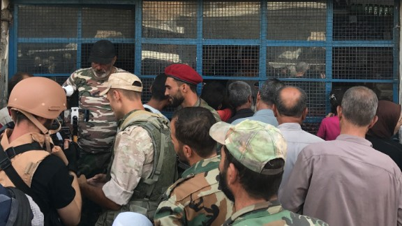 People line up outside a small store in central Deir Ezzor.