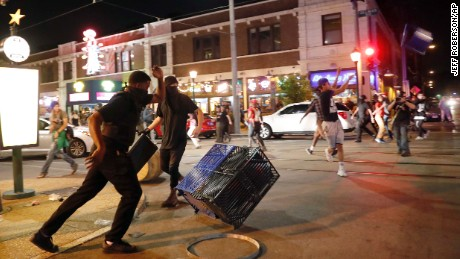 People overturn trash cans and throw objects as police try to clear a violent crowd Saturday, Sept. 16, 2017, in University City, Mo. Earlier, protesters marched peacefully in response to a not guilty verdict in the trial of former St. Louis police officer Jason Stockley. (AP Photo/Jeff Roberson)