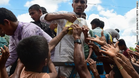 Rohingya refugees from Myanmar grab onto a bag of food from a man on a truck delivering aid in Ukhia on September 14.