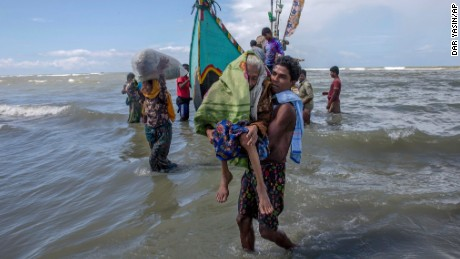 A Rohingya Muslim man walks to shore carrying an elderly woman after they arrived on a boat from Myanmar to Bangladesh in Shah Porir Dwip, Bangladesh, Thursday, Sept. 14, 2017. Nearly three weeks into a mass exodus of Rohingya fleeing violence in Myanmar, thousands were still flooding across the border Thursday in search of help and safety in teeming refugee settlements in Bangladesh. Those who arrived Wednesday in wooden boats described ongoing violence in Myanmar, where smoke could be seen billowing from a burning village, suggesting more Rohingya homes had been set alight. (AP Photo/Dar Yasin)