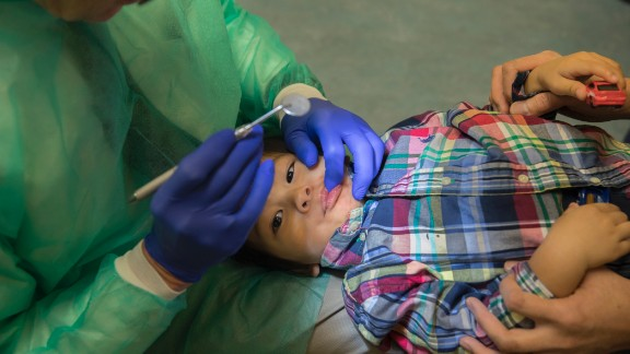 Ray Stewart, a pediatric dental professor at the University of California-San Francisco, examines Matthew Mai, 2, of Vallejo, Calif., at UCSF Benioff Children's Hospital San Francisco on Sept. 11, 2017. He emphasizes to parents of his young patients that dental decay is an infectious disease, so they should avoid sharing utensils with their kids. (Robert Durell for Kaiser Health News)