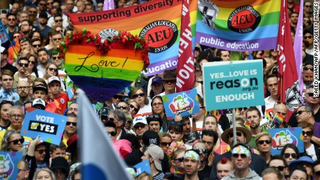 Supporters of marriage equality hold placards as they attend a rally in Sydney on September 10, 2017.
