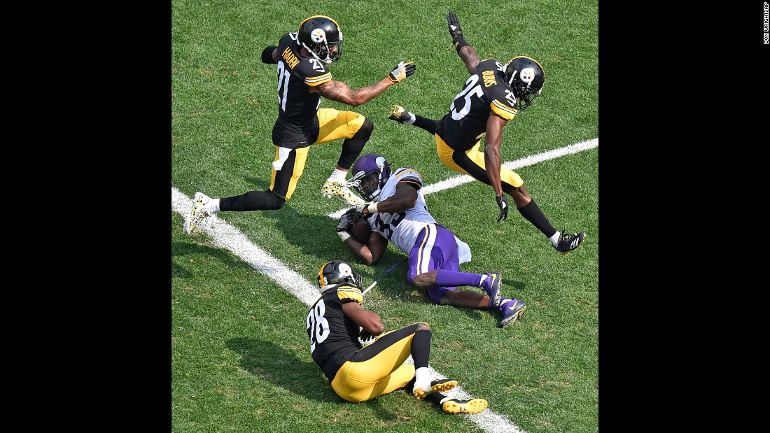 Pittsburgh defensive backs Joe Haden and Artie Burns leap over Minnesota running back Dalvin Cook after Cook was tackled just short of the goal line on Sunday, September 17.