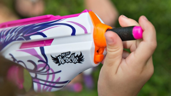 A young girl loads a foam bullet into a Hasbro Inc. Nerf Rebelle toy gun in Tiskilwa, Illinois, U.S., on Thursday, July 16, 2015. Hasbro Inc. is expected to report quarterly earnings on July 20, 2015. Photographer: Daniel Acker/Bloomberg via Getty Images