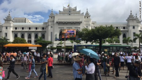 News crews and locals gather outside Yangon City Hall to watch Aung San Suu Kyi's speech on the big screen, on September 29.