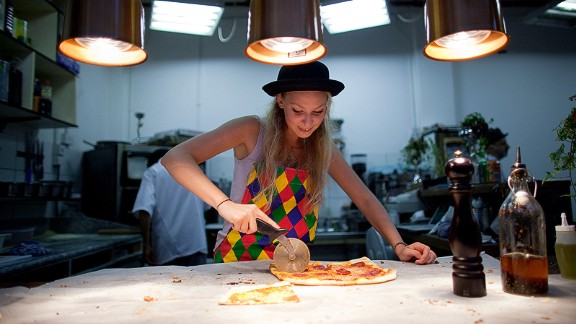 A woman serves pizza in London.