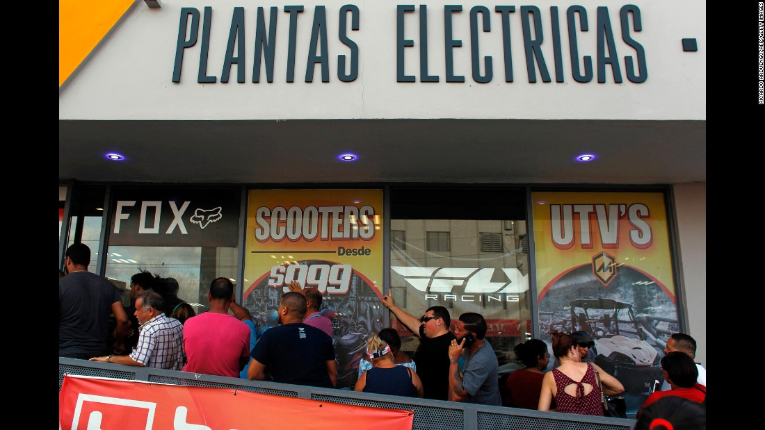 Customers wait in line for power generators at a store in San Juan on September 18.