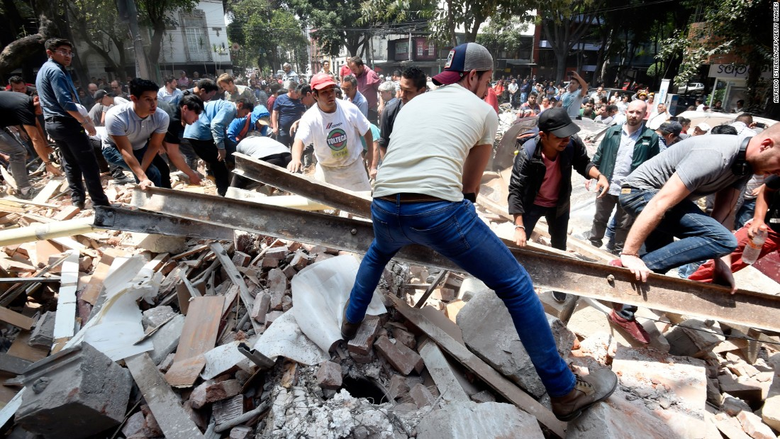 people remove debris off a building that collapsed in mexico city