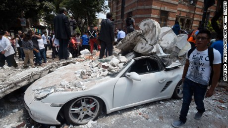 A man stands next to a car crashed by debris from a damaged building after a quake rattled Mexico City on September 19, 2017. A powerful earthquake shook Mexico City on Tuesday, causing panic among the megalopolis' 20 million inhabitants on the 32nd anniversary of a devastating 1985 quake. The US Geological Survey put the quake's magnitude at 7.1 while Mexico's Seismological Institute said it measured 6.8 on its scale. The institute said the quake's epicenter was seven kilometers west of Chiautla de Tapia, in the neighboring state of Puebla.  / AFP PHOTO / Alfredo ESTRELLA        (Photo credit should read ALFREDO ESTRELLA/AFP/Getty Images)