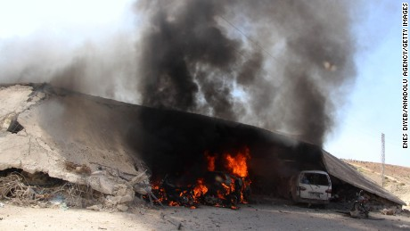 Burning vehicles are seen under the debris of Al-Rahma Hospital.