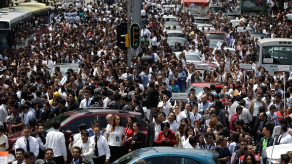 People gather on a Mexico City street after office buildings were evacuated because of the quake.