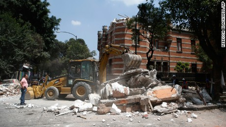 A bulldozer removes debris from a partially collapsed building after an earthquake in Mexico City on September 19.