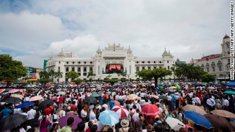 People gather to listen to the live speech of Myanmar's State Counselor Aung San Suu Kyi in front of City Hall in Yangon on September 19, 2017.