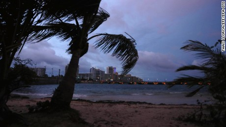 "Palm trees blow in the wind late Tuesday in San Juan, Puerto Rico, where the governor warned that the island faced an ""imminent danger"" from Hurricane Maria."