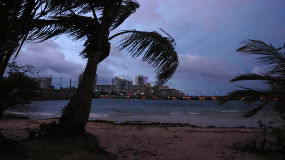 """Palm trees blow in the wind late Tuesday in San Juan, Puerto Rico, where the governor warned that the island faced an """"imminent danger"""" from Hurricane Maria."""