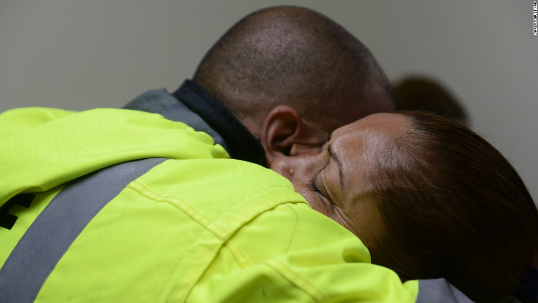 Members of a rescue team embrace as they wait to help in Humacao on September 20.